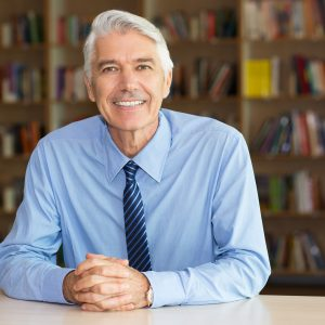 Portrait of senior Caucasian businessman or teacher wearing shirt and tie sitting at workplace in library, looking at camera and smiling